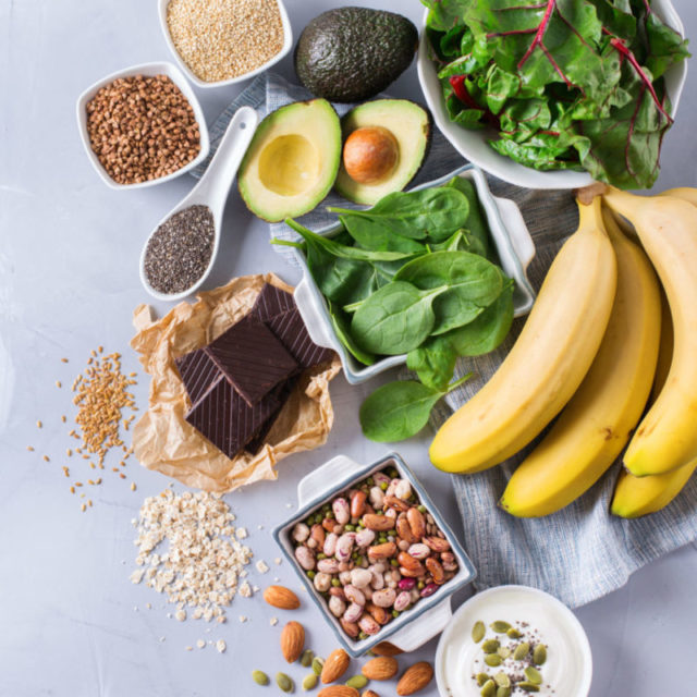 80990958 - healthy food nutrition dieting concept. assortment of high magnesium sources. banana chocolate spinach chard, avocado, buckwheat, sesame chia flax seeds, yogurt, nuts, beans oat